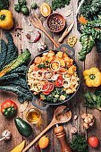 Pot with sliced colorful vegetables and cooking utensils on rustic wooden background. Top view. Organic vegetarian ingredients and kitchen tools. Healthy, clean food and eating concept. Zero waste