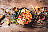 Big pot with sliced colorful vegetables and cooking utensils on rustic wooden background. Top view. Organic vegetarian ingredients and kitchen tools. Healthy, clean food and eating concept. Zero waste