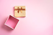 Valentine's Day. Golden gift box on pink background. Top view. Copy space. Festive backdrop for holidays: Birthday, Valentines day, Christmas, New Year. Flat lay style. Banner