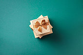 Valentine's Day. Golden gift box on green background. Top view. Copy space. Festive backdrop for holidays: Birthday, Valentines day, Christmas, New Year. Flat lay style. Banner