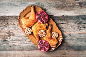 Roasted chicken with pomegranate and garlic on wooden background. Friends or family dinner. Festive Christmas table. Top view. Traditional Thanksgiving or Friendsgiving holiday celebration dish.