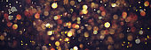 Golden shiny glitter, sparkles, light bokeh on dark background. New year, Christmas background. Banner with copy space. Festive backdrop for greeting card