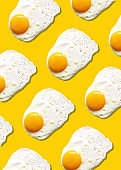 Fried egg or scrambled eggs pattern on yellow background. Creative food concept. Top view. Conceptual trend. Banner. Keto diet. Healthy food print. Creative design for packaging.