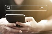 People hand using mobile phone or smartphone searching for information in internet online society web with search box icon and copyspace.