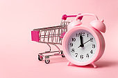 Close-Up Of Alarm Clock and Shopping Cart Against Pink Background. Sale, discount time, time saving concept. Top view, flat lay with copy space.