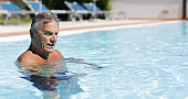 Senior man swimming in a swimming pool: summer relax with social distancing