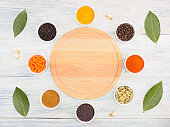 Round kitchen cutting board and ingredients for cooking: black pepper, turmeric, chili, green grass, masala, cumin (jeera), cardamom, carrot, dry onion, herb, salt, garlic, bay leaves. Healthy eating concept