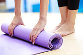 Close-up of attractive young woman folding blue yoga or fitness mat after working out at home in living room.