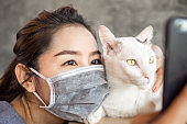 Asian woman wearing medical mask and playing and hug her cat during covid-19 outbreak, social distancing and new normal lifestyle concept