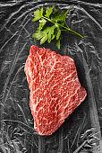 Kobe beef tenderloin marbled meat with parsley on plastic foil