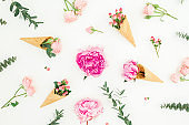 Floral spring composition with pink peonies, roses petals, eucalyptus, waffle cones on white. Flat lay