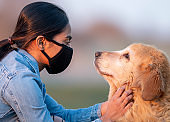 Middle Eastern Female Wearing a Mask while Playing with Dog