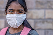 Beautiful Indian girl wearing a mask to go back to school