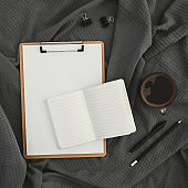 Mug of coffee with clipboard, diary and pen on gray plaid. Flat lay, top view. Stay at home.