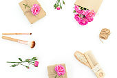 Beauty frame composition of pink roses with hairbrush, tassel and gifts box on white background. Flat lay, top view