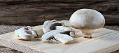 Closeup of raw whole champignons on wooden cutting board, natural sackcloth and piese of wood background. Artificially grown mushrooms. Vegetarian food. Selective focus