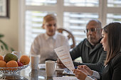 Financial advisor meets with couple in their home to discuss plans for the future