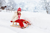 Girl on sleigh ride. Kids sled. Child with sledge