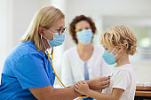 Doctor examining sick child in face mask