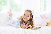 Child reading book in bed. Kids read in bedroom.