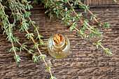 A bottle of essential oil with thyme twigs