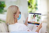 Sick woman in face mask calling doctor.