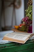 Old open book on windowsill or desk with daylight, defocused background