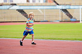 Child running in stadium. Kids run. Healthy sport.