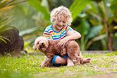 Kids play with puppy. Children and dog in garden.