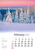 Calendar February 2021, vertical B3 size. Set of calendars with amazing landscapes. Picturesque winter view of mountain forest. Spectacular sunrise in Carpathian mountains, Ukraine, Europe.