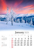 Calendar January 2021, vertical B3 size. Set of calendars with amazing landscapes. Stunning winter view of mountain forest. Colorful sunrise in Carpathian mountains, Ukraine, Europe.
