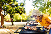 Senior women cooking meat on a smoky barbecue in the garden on a sunny afternoon