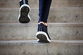 Sport hard. Close up of male feet climbing stairs outside. Well shaped man is jogging at dawn