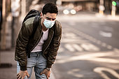 Man suffer from cough with face mask protection,wearing face mask because of air pollution in the city building,Sick man with medical mask;concept of pollution,dust allergies