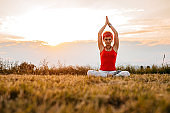 Pretty woman meditating on meadow