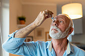 An old man implementing eyedrops to his eye