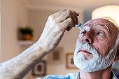 Man putting liquid drops in his eye solving vision problem. Senior man using eye drops