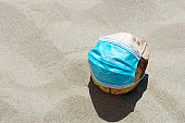 Green Coconut on a sandy beach with protective mask. Copy space.