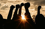 Silhouette of raised fists at sunset
