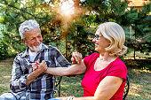 Senior couple sitting in backyard drinking coffee