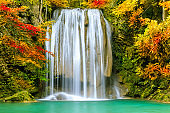 Colorful majestic waterfall in national park forest during autumn