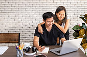 Asian woman wife motivate advice man husband freelancer working at home, sitting at desk dining table in living room
