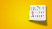 2021 December Calendar on Note Pad Against Yellow Background
