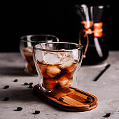 Iced coffee in a glass with ice cubes on wooden tray,scattered grains on concrete background