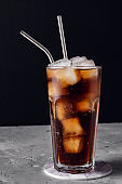 Glass glass with soda and ice ,metal reusable straw for cocktails