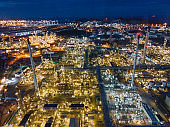 Oil refinery plant from industry zone, Aerial view oil and gas petrochemical industrial, Refinery factory oil storage tank and pipeline steel at night, Ecosystem and healthy environment concepts.