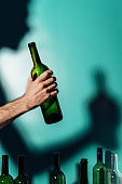 Silhouette of a man holding a bottle of alcohol in his hand, alcohol addiction concept