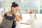Latin Woman Feeling Stressed And Fatigued using laptop for doing work at home and  text message on social network