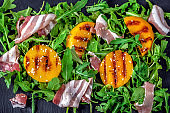 Delicious salad with grilled peaches and prosciutto