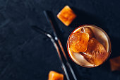 Iced coffee in a glass with ice cubes on black wooden background,metal zero waste straw for cocktails, copy space,top view